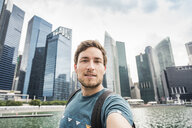 Tourist posing in front of Singapore skyline, Marina Bay - CUF21271
