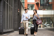 Young businessman and woman with wheeled suitcases walking and talking, London, UK - CUF21316