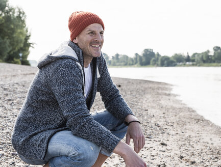 Smiling mature man with red beanie at Rhine riverbank - UUF13965