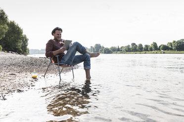 Mature man using tablet at Rhine riverbank - UUF13971