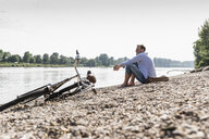 Mature man with bike sitting at Rhine riverbank - UUF13980
