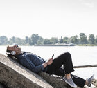 Mature man with headphones and smartphone at Rhine riverbank - UUF13989