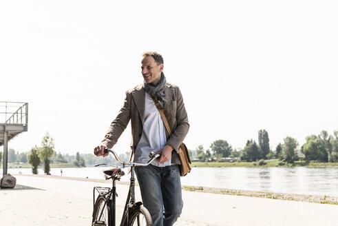 Mature man with bike at Rhine riverbank - UUF13998