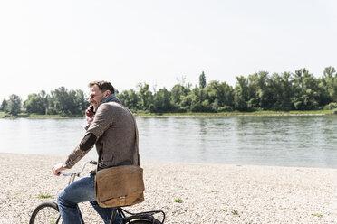 Mature man with bike using smartphone at Rhine riverbank - UUF14007