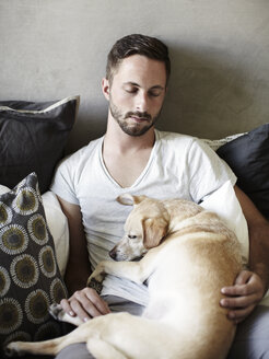 Young man and dog asleep on bed - ISF07598