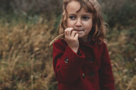 Portrait of girl chewing long grass in field - ISF07637