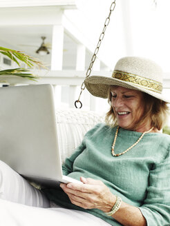 Senior woman relaxing outdoors, using laptop - ISF07667