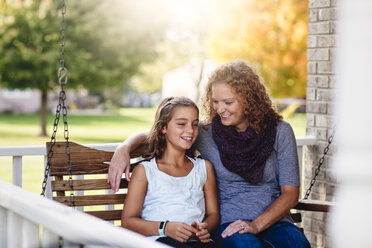 Aunt and niece sitting on porch swing, smiling - ISF07709