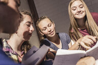 Teenagers reading notes in high school study group - ISF07841