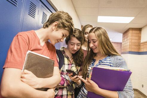 Teenagers looking at smartphone in high school locker room - ISF07859