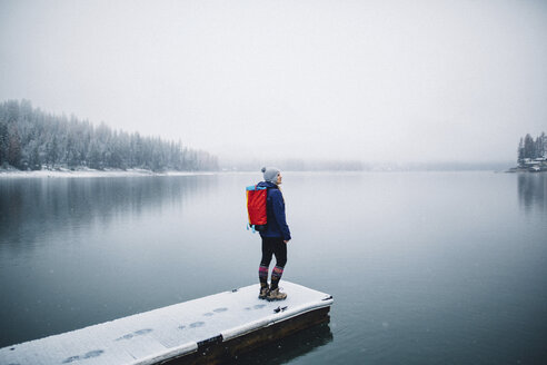 Hiker on snow covered pier looking at view of lake, Bass Lake, California, USA - ISF07895