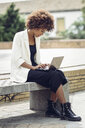 Fashionable young woman with curly hair sitting on bench using laptop - JSMF00214