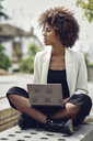 Fashionable young woman with curly hair sitting on bench with laptop - JSMF00217
