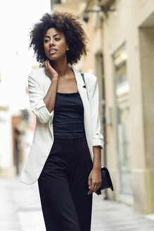 Portrait of fashionable young woman with curly hair walking in the city - JSMF00223