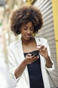 Portrait of smiling young woman with curly hair looking at cell phone - JSMF00226