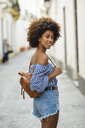 Portrait of fashionable young woman with small backpack on the street - JSMF00238