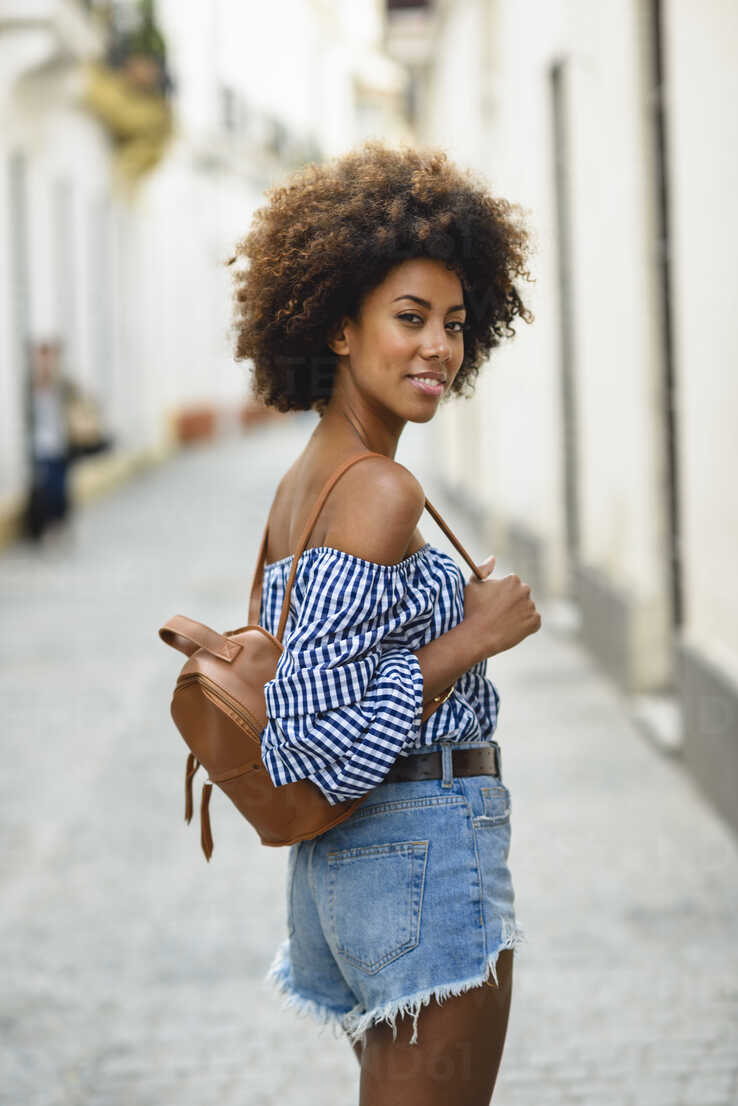 Portrait of fashionable young woman with small backpack on the street - JSMF00238 - Javier Sánchez Mingorance/Westend61