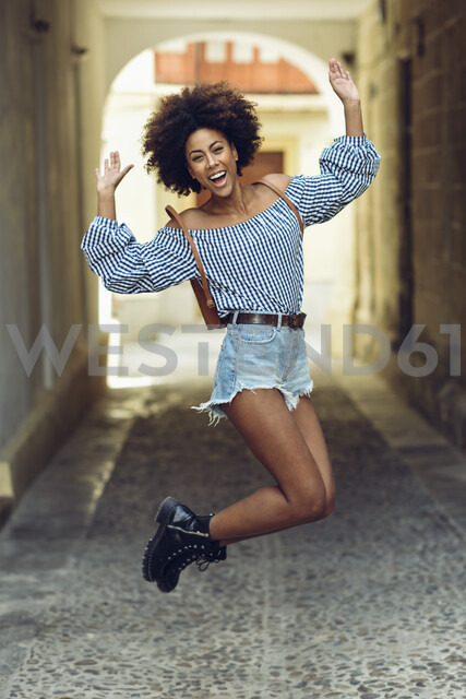 Portrait of laughing young woman jumping in the air - JSMF00244