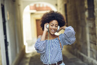 Portrait of happy young woman listening music with headphones - JSMF00247
