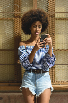 Portrait of fashionable young woman with curly hair looking at smartphone - JSMF00253