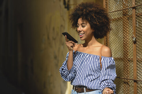 Portrait of fashionable young woman with curly hair on the phone - JSMF00256