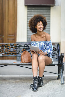 Young woman sitting on bench in the city using tablet - JSMF00259