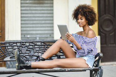 Young woman sitting on bench in the city using tablet - JSMF00262