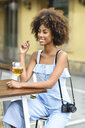 Portrait of fashionable young woman with camera drinking beer outdoors - JSMF00268