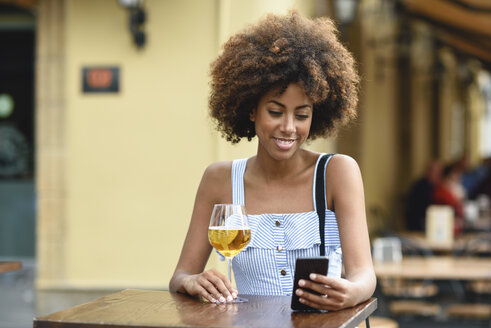 Portrait of young woman with smartphone drinking beer outdoors - JSMF00271