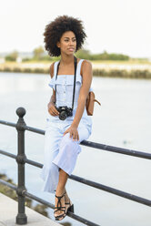 Portrait of fashionable young woman with camera and backpack - JSMF00274