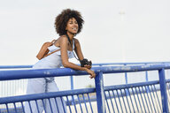 Portrait of fashionable young woman with backpack and camera on a bridge - JSMF00277