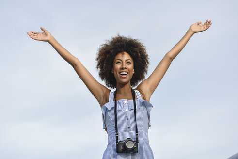 Portrait of happy young woman with camera against sky - JSMF00283