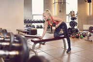 Woman working out with dumbbells in gym - CUF21393