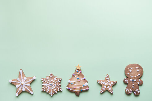 Row of five gingerbread cookies decorated with sugar icing on bright green background - SKCF00460