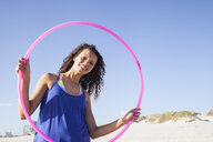 Woman on beach looking through hula hoop at camera smiling - CUF21472