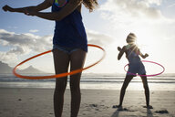 Young women on beach using hula hoops - CUF21481