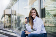 Portrait of smiling young businesswoman with coffee to go - DIGF04563