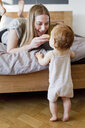Mid adult woman feeding baby daughter a biscuit from bed - CUF21723