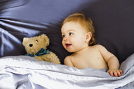 Baby girl lying in bed with teddy bear - CUF21753