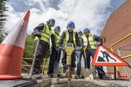Apprentice builders training with pneumatic drill in training facility - CUF21822