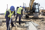 Apprentice builders laying concrete foundations on building site - CUF21828