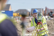 Apprentice builders using theodolite on building site - CUF21837