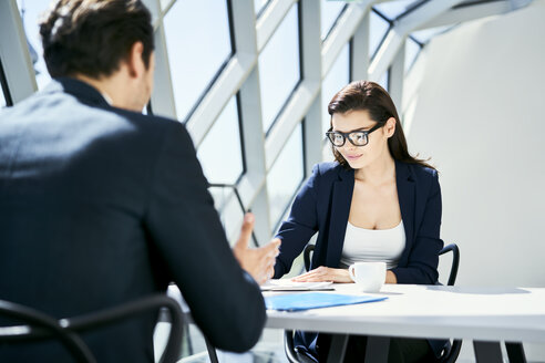 Businesswoman and businessman talking at desk in modern office - BSZF00456