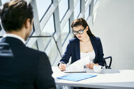 Businesswoman with businessman at desk checking documents in modern office - BSZF00459