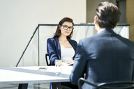 Businesswoman and businessman talking at desk in modern office - BSZF00462