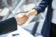 Close-up of handshake of businesswoman and businessman - BSZF00465