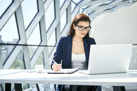 Businesswoman working at desk in modern office - BSZF00471