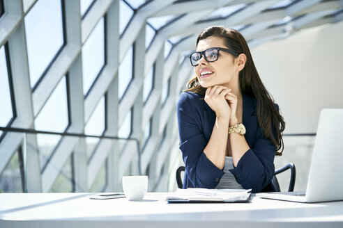 Smiling businesswoman sitting at desk in modern office - BSZF00474