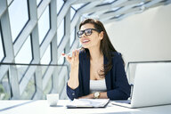 Smiling businesswoman sitting at desk in modern office using smartphone - BSZF00477