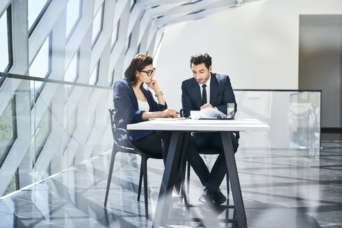 Businesswoman and businessman checking documents at desk in modern office - BSZF00489